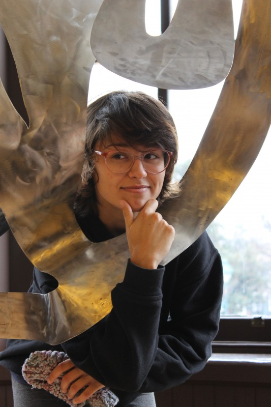 A medium-skinned, dark and short haired woman with her hands up in a thinking pose and head sticking out of the metal sculpture looks to the corner pensively with glasses on.